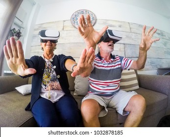 Couple of aged man and woman senior elderly play at home on the sofa with goggles headset trying virtual reality video games and vides. Activityies at home for  60 years old concept