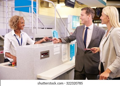 Couple At Airport Check In Desk Leaving On Business Trip