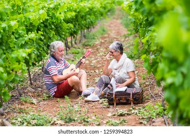 couple of alternative aged older traveler stay sitting down in a vineyard with the luggage and playing an ukulele acoustic guitar and reading a paper book. easy lifestyle in outdoor places nature feel