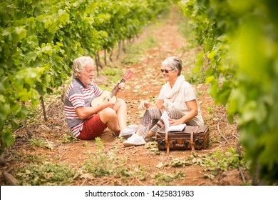 couple of alternative aged older traveler stay sitting down in a vineyard with the luggage and playing an ukulele acoustic guitar and reading a paper book. easy lifestyle in outdoor places and nature