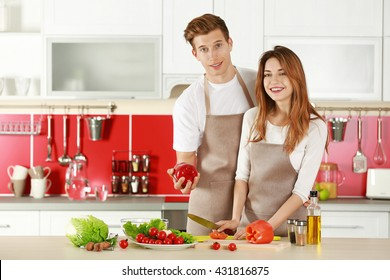 Couple in aprons cooking in kitchen