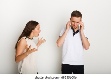 Couple arguing. Angry woman shouting to boyfriend, he covering ears with hands, copy space