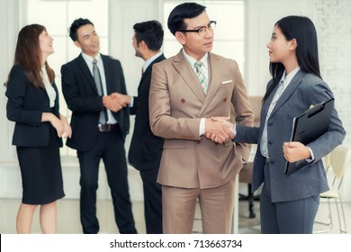 Couple of Asian business people with casual wear talking with happy and shaking hand in modern Office or coffee shop. Business sucess concept