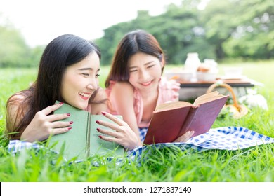 couple asian female picnic in the public garden, they rest on floor covering and reading a book and connect internet with laptop, they smile and feeling happy