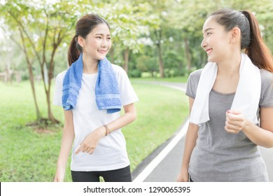 couple asian female running on the way, in public park, they break and resting , health promotion, attractive asian woman exercise and smile