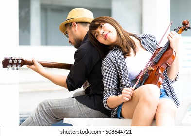 A couple of asian lover relaxing playing a music, men with guitar, women with a violin