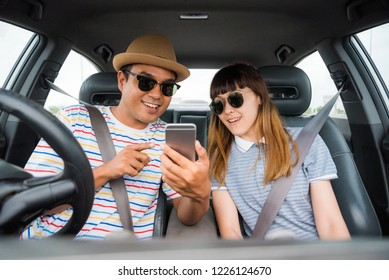 Couple asian man and woman sitting in car and looking at smartphone. Travel concept.