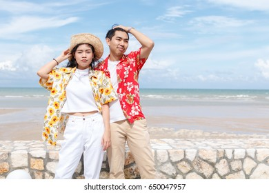 couple asian man and woman wear yellow and red shirt on the beach, beautiful sky background