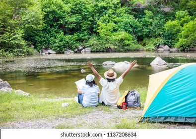 couple asian senior people travel in forest, they camping at lakeside , retirement activity, adventure and travel