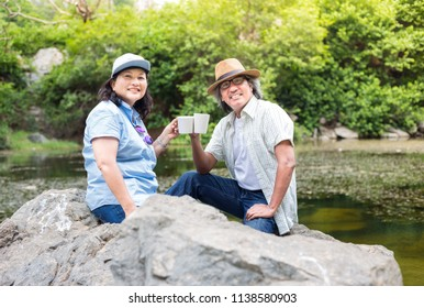 couple asian senior people travel in forest, they drinking hot coffee at lakeside , retirement activity, adventure and travel