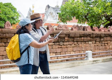couple asian senior people travel at asian archaeological site, asian culture, travel and adventure