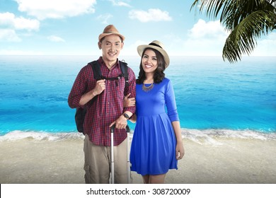 Couple asian tourist standing on the beach with blue sky background