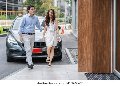 Couple asian walking into the car showroom for checking their grey color car,  Customer and maintainance service concept