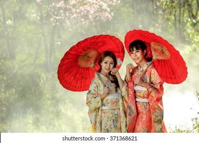 Couple asian women wearing traditional japanese kimono and red umbrella in the himalayan sakura garden,Thailand.
