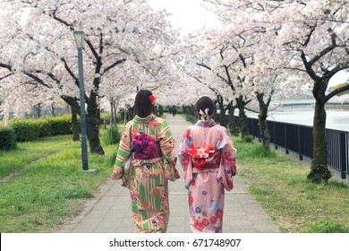 Couple asian women wearing traditional japanese kimono in sakura garden in Osaka, Japan
