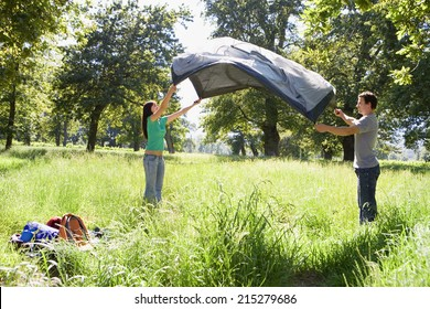 Couple assembling tent on camping trip in woodland clearing, side view