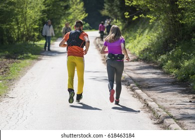 Couple athlete running on forest trail. Fitness jogging workout wellness concept.