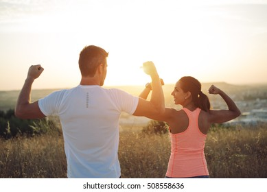 Couple of athletes flexing biceps towards the sunset. Couple of athletes celebrating running outdoor workout success.