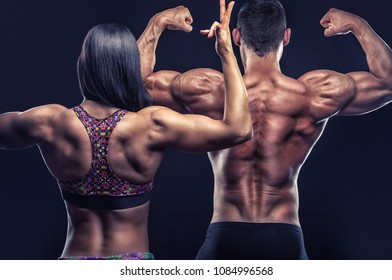 Couple of athletes posing in front of the camera showing their athletic backs and hands on a black background