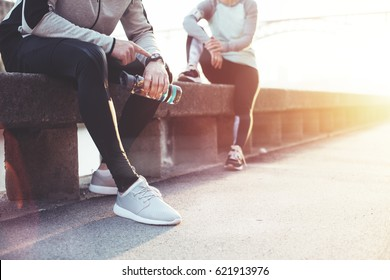 Couple of athletes resting after workout session on the street. Tired man with bottle tracking time with his watch and woman relaxing on the bench