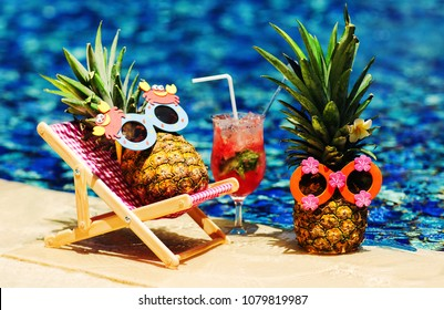 Couple of attractive pineapples in cheerful sunglasses lying on sunchair near the turquoise swimming pool. Relaxing, drinking fresh juice. Tropical summer vacation concept. Happy sunny day. Sunbathing