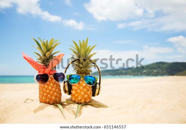 Un par de bonitas piñas enamoradas en la arena contra el mar turquesa. Con elegantes gafas de sol espejadas. Concepto de vacaciones de verano tropical. Día soleado en la playa de la isla tropical. Luna de miel