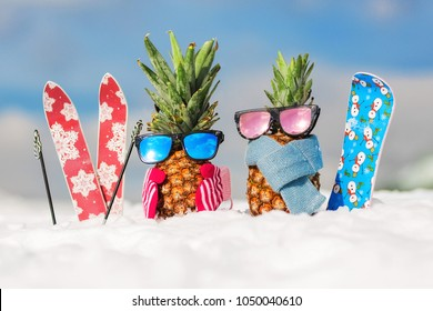 Couple of attractive pineapples in stylish mirrored sunglasses on the snow in the mountain. Winter ski holidays concept. Wearing mittens, scarf. Mountain skiing, snowboard outfit. Family holiday
