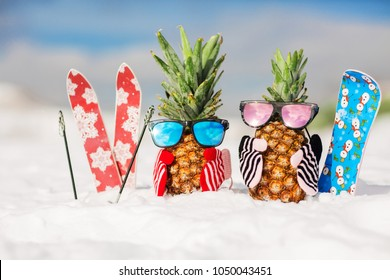 Couple of attractive pineapples in stylish mirrored sunglasses on the snow in the mountain. Winter ski holidays concept. Wearing stylish mittens. Mountain skiing, snowboard outfit. Family holiday