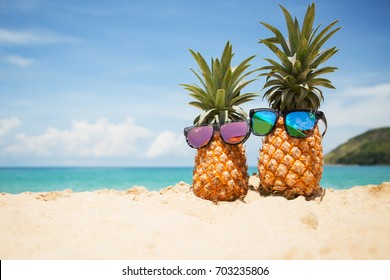 6c430b60b9 Couple of attractive pineapples in stylish mirrored sunglasses on the sand  against turquoise sea. Tropical