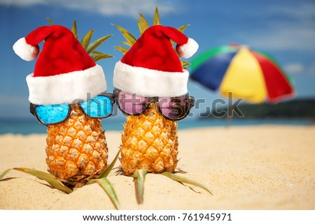 8bc13164 Couple of attractive pineapples in stylish mirrored sunglasses on sand  against turquoise sea and beach umbrella. Wearing christmas hat. Christmas  and new ...
