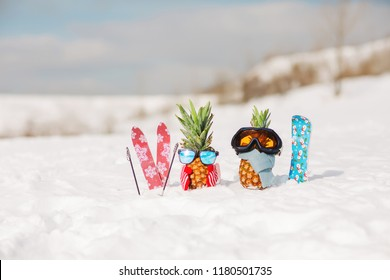 Couple of attractive pineapples in stylish sunglasses, ski goggles  on the snow in the mountain. Winter ski holidays concept. Wearing mittens, scarf. Mountain skiing, snowboard outfit. Family holiday