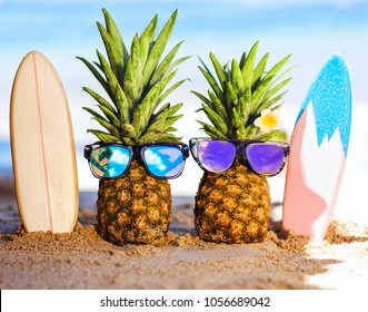 Couple of attractive pineapples surfers in stylish sunglasses on the sand against turquoise sea. Having stylish surfboards. Tropical summer vacation concept. Sunny day on the beach. Family holiday