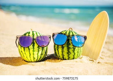 Couple of attractive watermelons surfers in stylish mirrored sunglasses on the sand against turquoise sea. Tropical summer vacation concept. Sunny day on the beach of tropical island. Honeymoon.