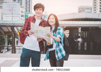 couple attractive young traveler beautiful asian woman and handsome caucasian man have smile happy and laugh funny with traveling in modern metropolis outdoor at Bangkok city Thailand.