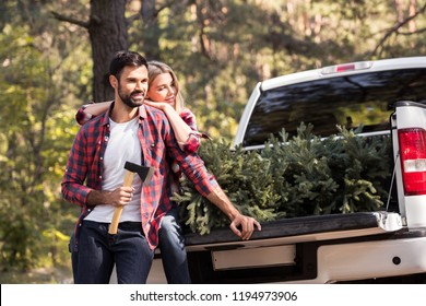 Couple with axe sitting on pickup truck with fir tree for christmas in forest
