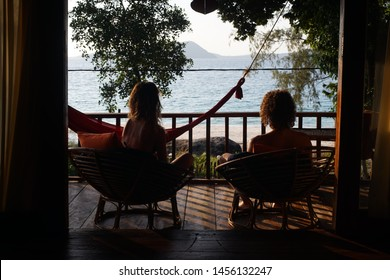 Couple from the back sitting on a bungalow balcony enjoying the sea view.