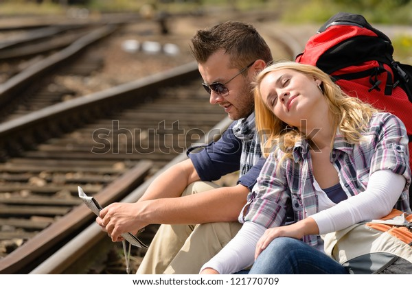 Couple backpack traveling resting on railroad map happy direction tired