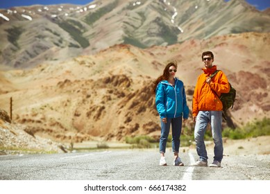 Couple of backpackers stands on mountain road and waiting for car