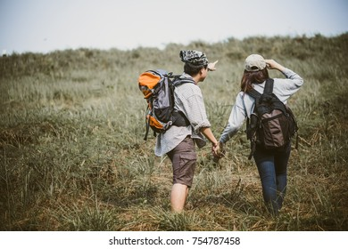 Couple of backpacking hikers going to mountain top and navigating by map paper. Backpackers or Hikers travel concept. Selective focus.
