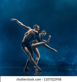 The couple of ballet dancers dancing under water drops and spray. Young caucasian and afro american models. Man and woman dancing together. Ballet and contemporary choreography concept. Art photo
