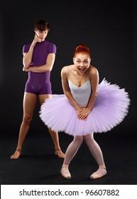 Couple of ballet dancers posing over dark background