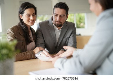 Couple in bank office signing loan agreement