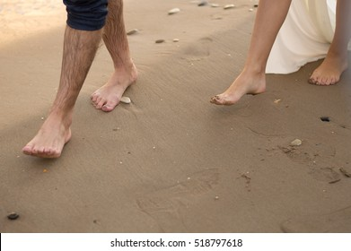 Couple. Bare feet. Footprints in the sand. Sea.