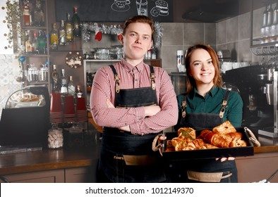 Couple of barista standing near bakery in coffee shop. Handsome man and attractive woman are making coffee. Food and drink industry concept