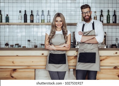 Couple of barista are working in coffee shop. Attractive young woman and handsome bearded man are standing together behind the bar counter