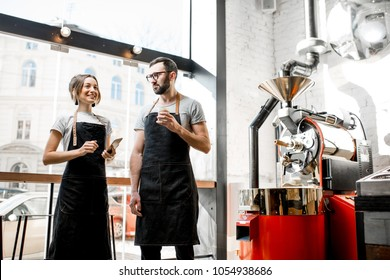 Couple of baristas talking during the coffee break standing together in the coffee shop with roaster machine on the background