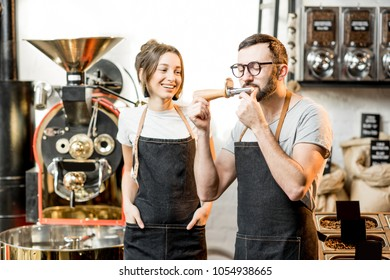 Couple of baristas in uniform checking the quality of roasted coffee beans standing near the roaster machine