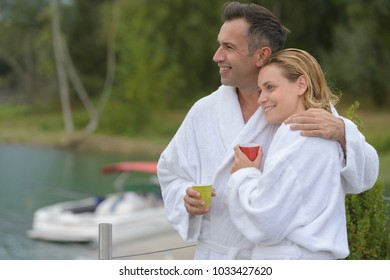 couple in bathrobe sitting on a pontoon