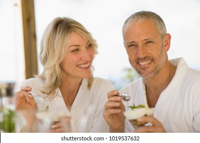 Couple in bathrobes having breakfast