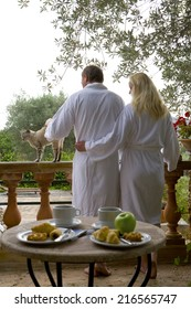 Couple in bathrobes petting cat on patio with breakfast in foreground